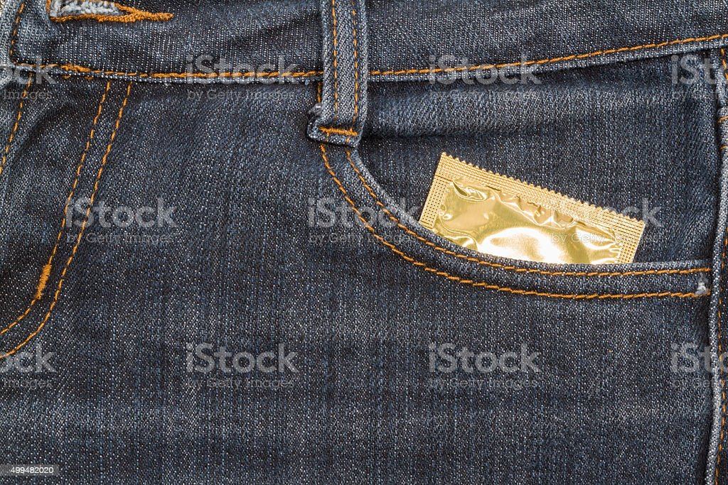 Condom in jeans pocket.  background. stock photo