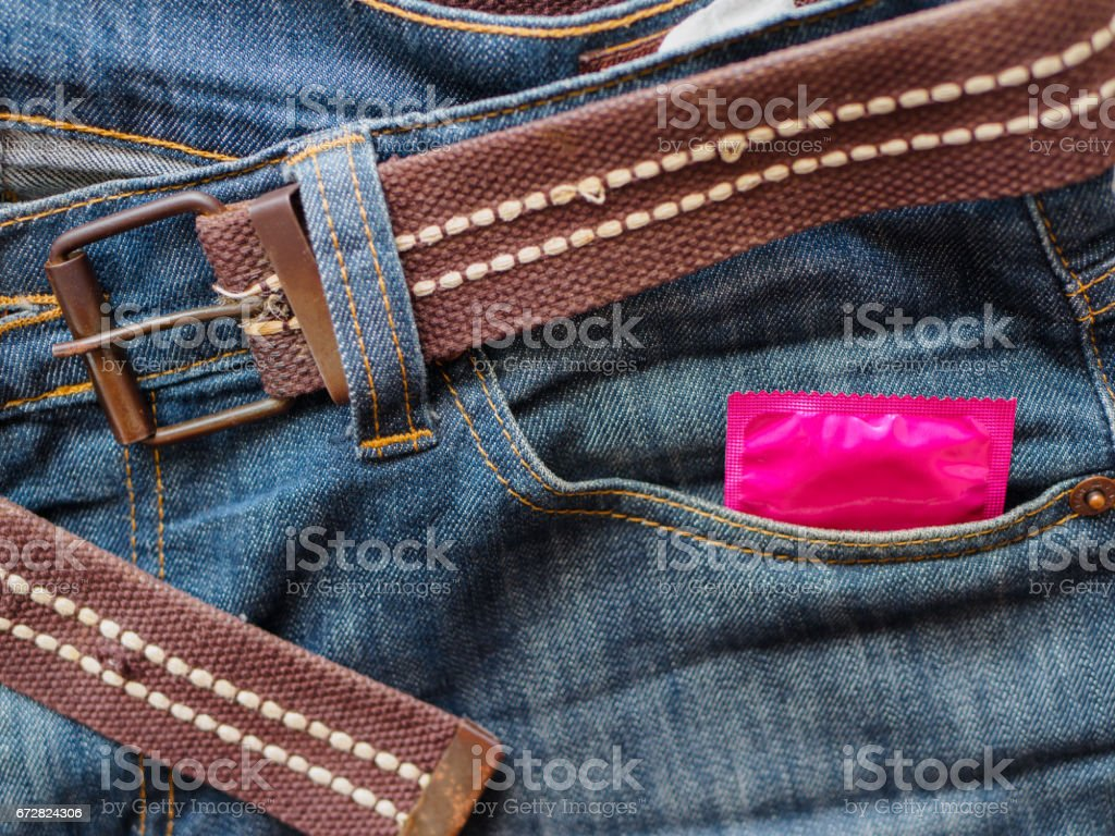 Condom in the blue jeans pocket stock photo