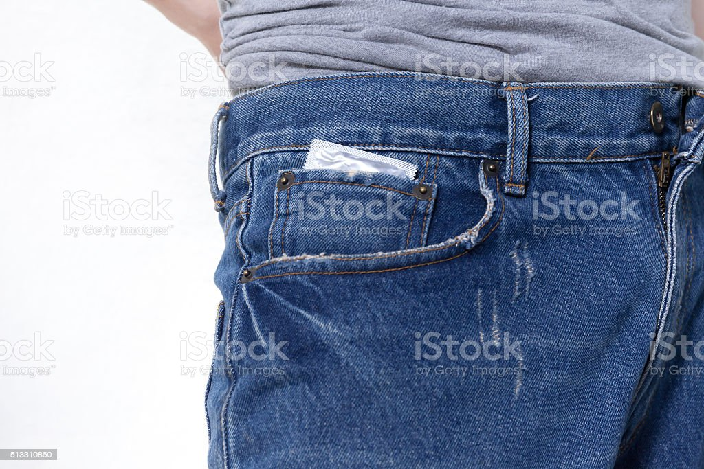 Condom in the pocket of blue jeans on isolated white stock photo