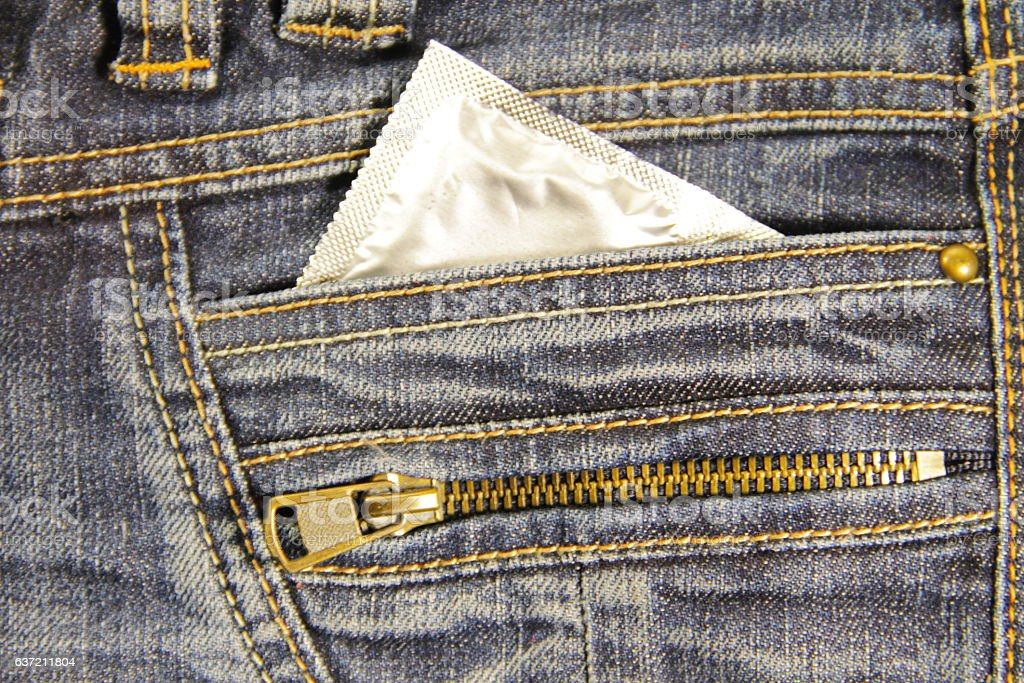 Condom in the pocket of the blue jeans stock photo