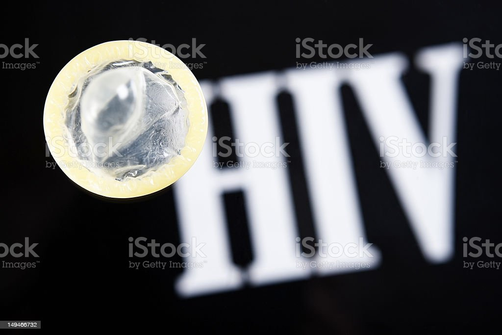 Condom sits on reversed out HIV against black royalty-free stock photo