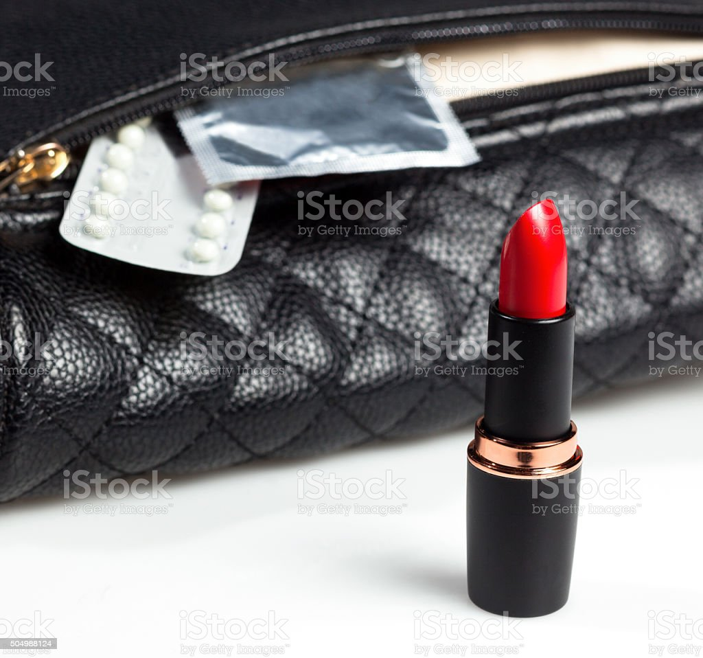 condoms, birth control pills and red lipstick stock photo
