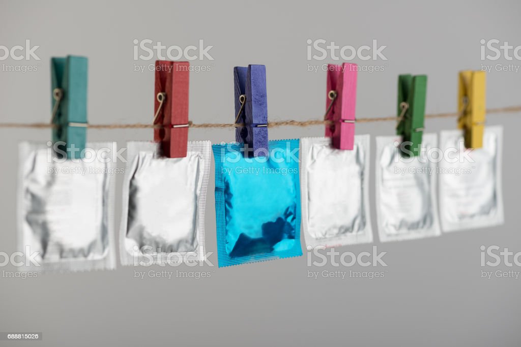 Condoms hanging on the rope on gray background. stock photo