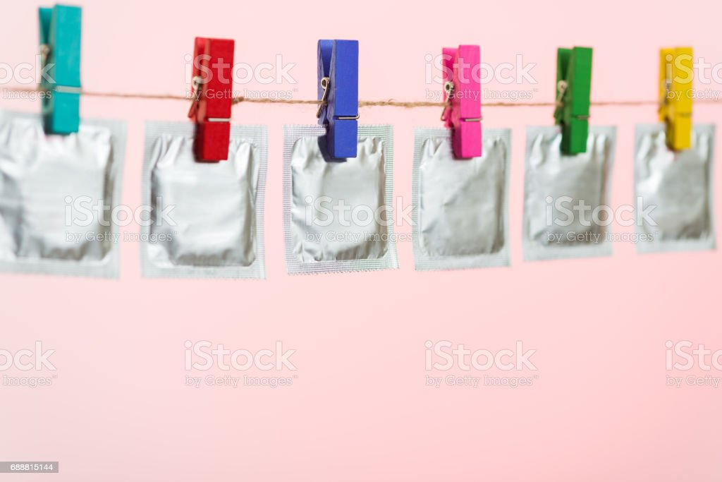 Condoms hanging on the rope on light pink background. stock photo