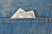 Condoms in the pocket of a blue jeans closeup