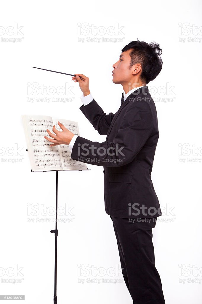 Conductor with music sheet and baton stock photo