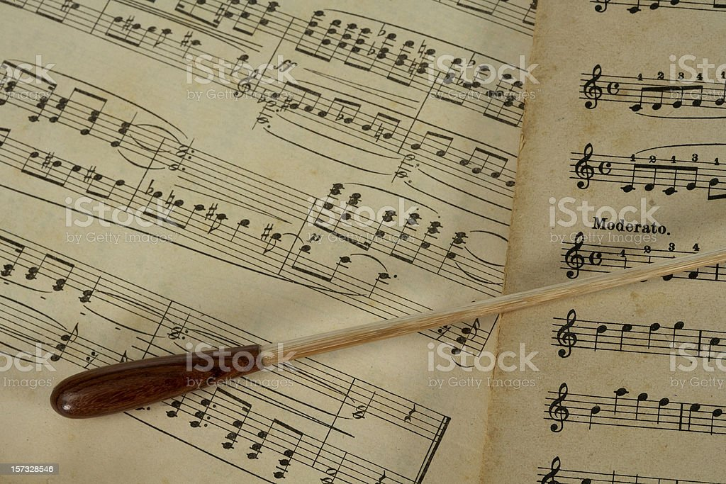 Conductors's baton lying on music notes horizontal stock photo