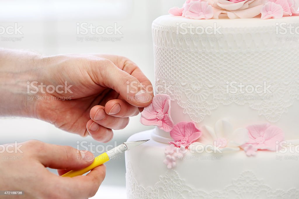 Confectioner decorates wedding cake stock photo