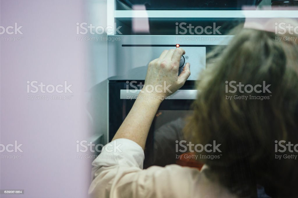 Confectioner switching oven on stock photo
