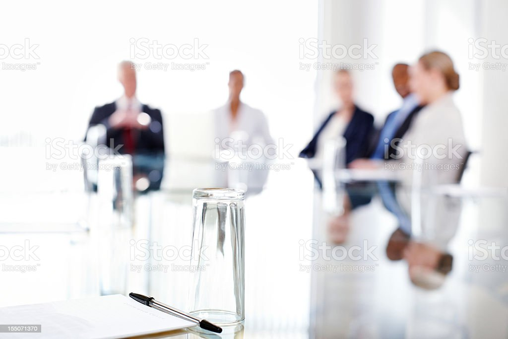 Conference Table With Business People Sitting in the Background stock photo