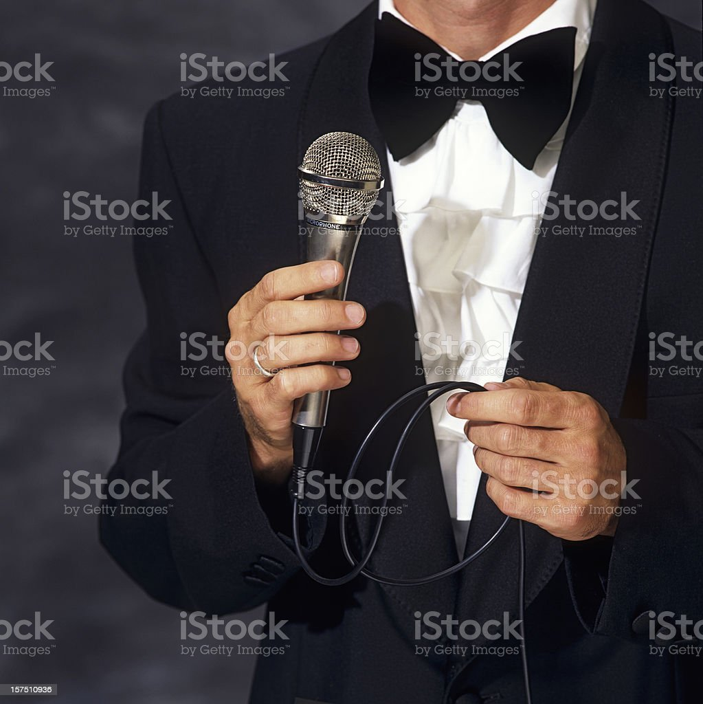 Conferencier in elegant suit holding the microphone stock photo