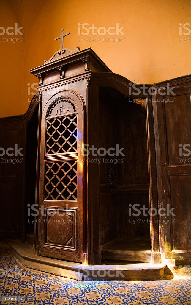 Confession Booth with Stained Glass Window Reflection stock photo