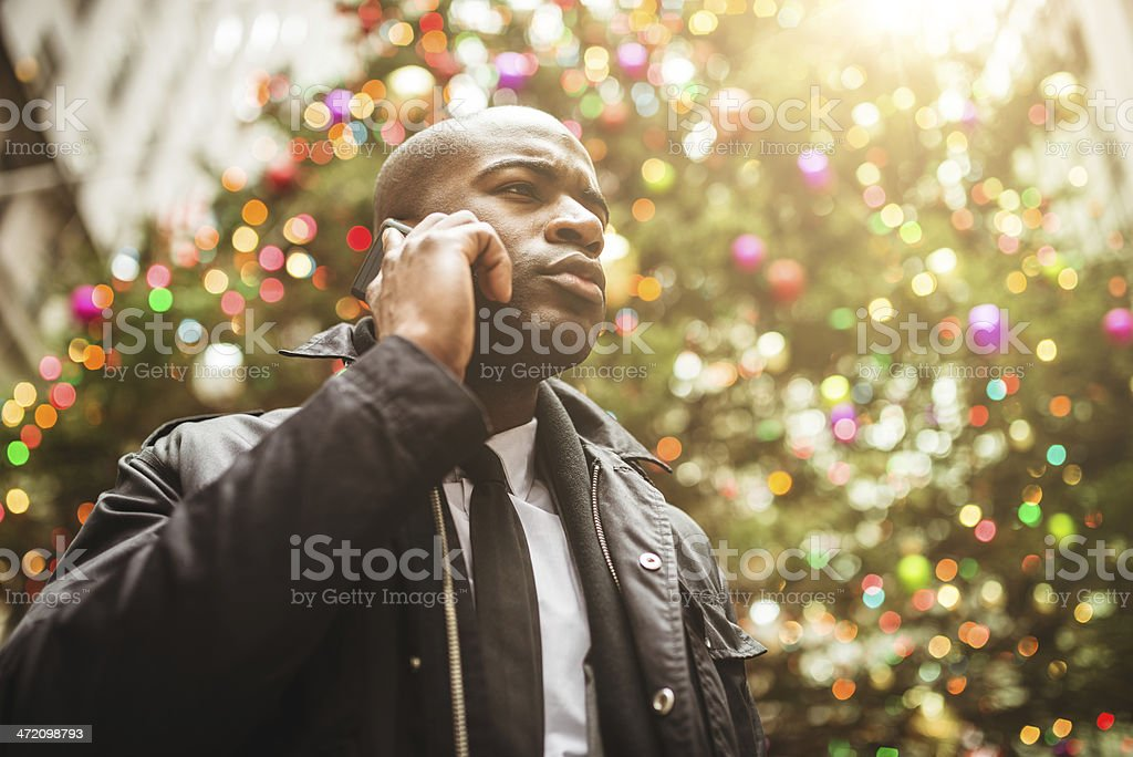 Confidence afro american broker standing against a christmas tree royalty-free stock photo