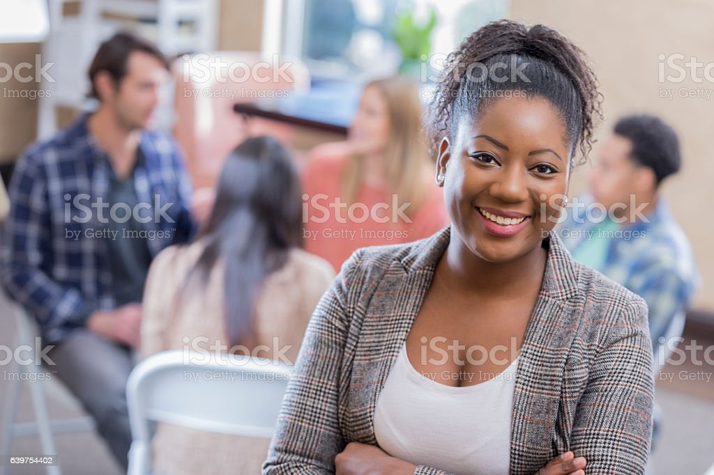 Confident African American counselor in front of support group stock photo