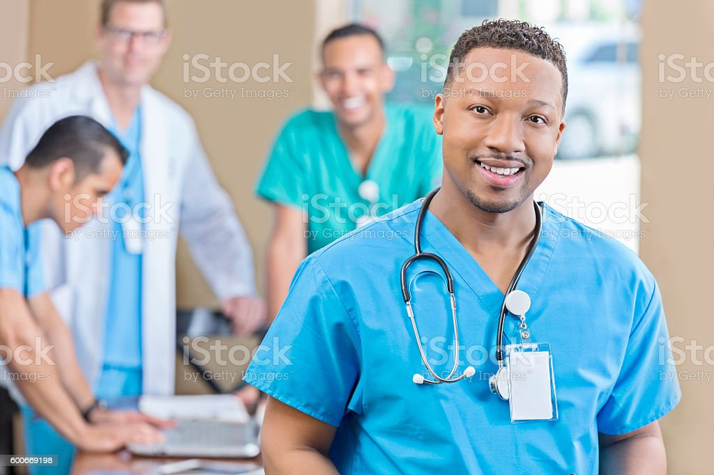 Confident African American male nurse at staff meeting stock photo