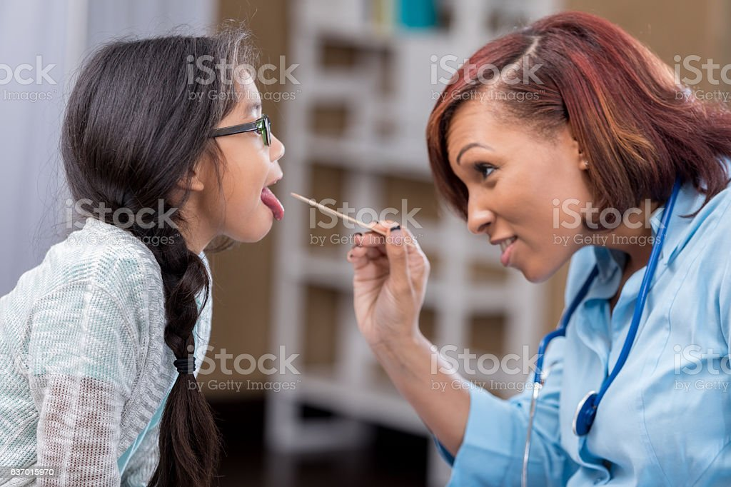 Confident African American pediatrician examines young Filipino patient stock photo