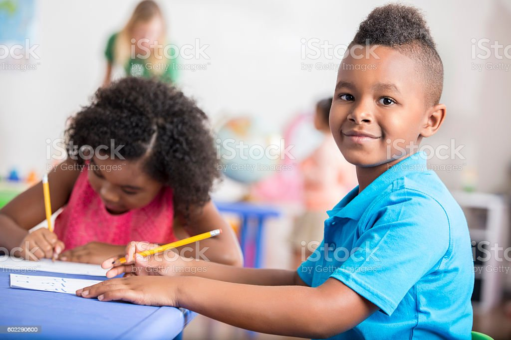 Confident African American student works in class stock photo