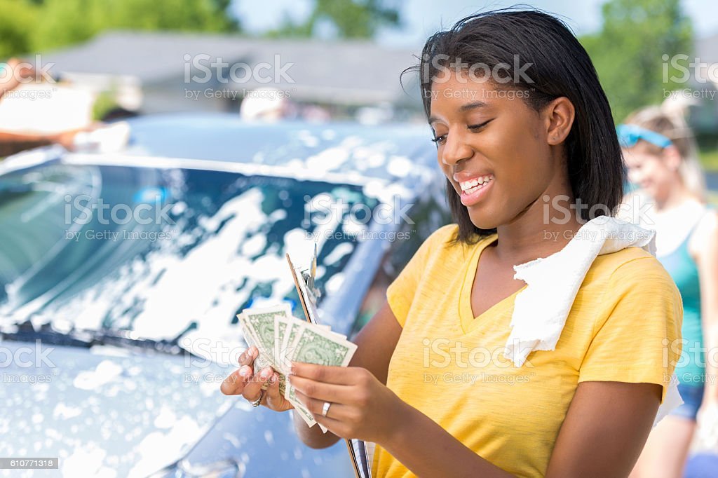 Confident African American teenage girl counts money at car wash stock photo