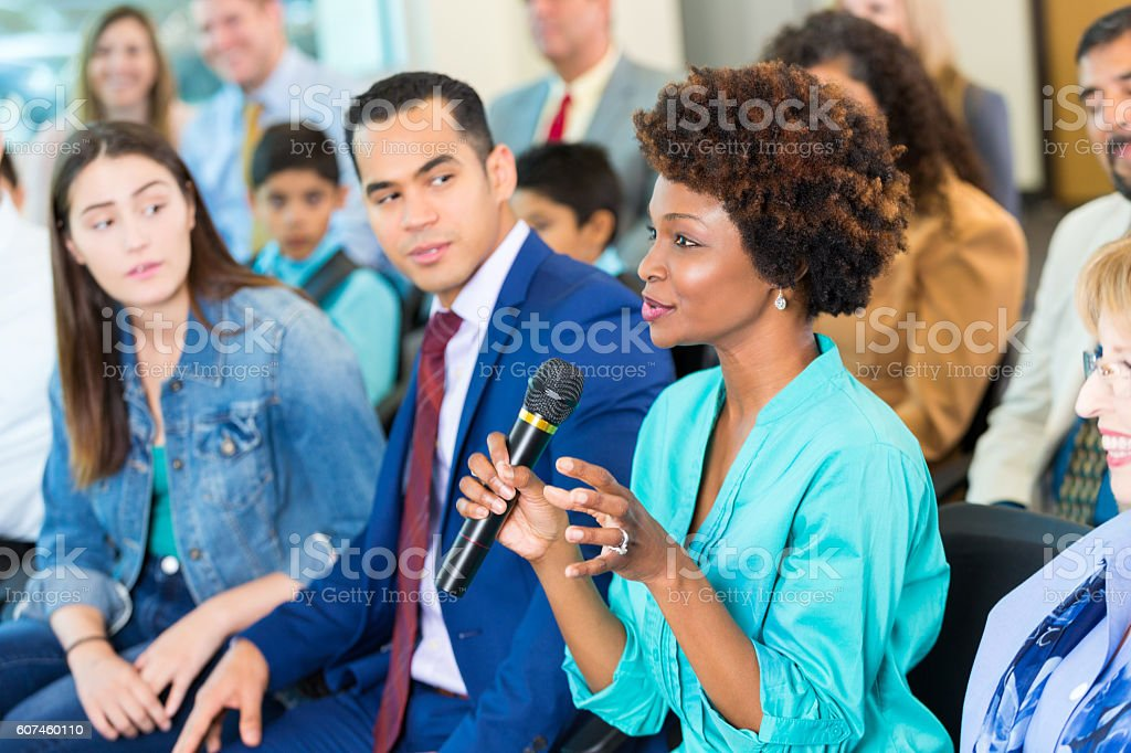 Confident African American woman asks question during a meeting stock photo