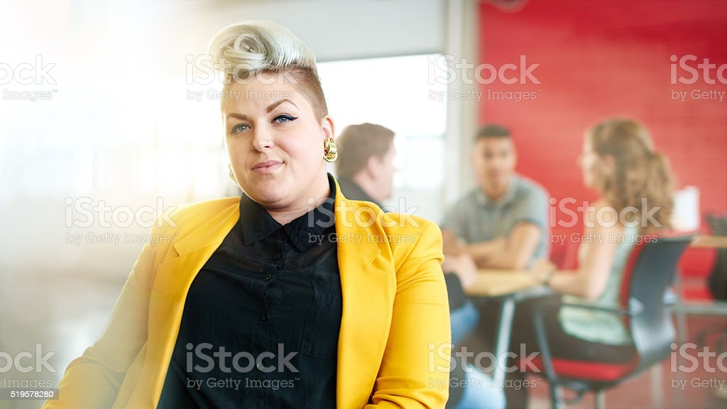 Confident and edgy female designer working on a digital tablet stock photo
