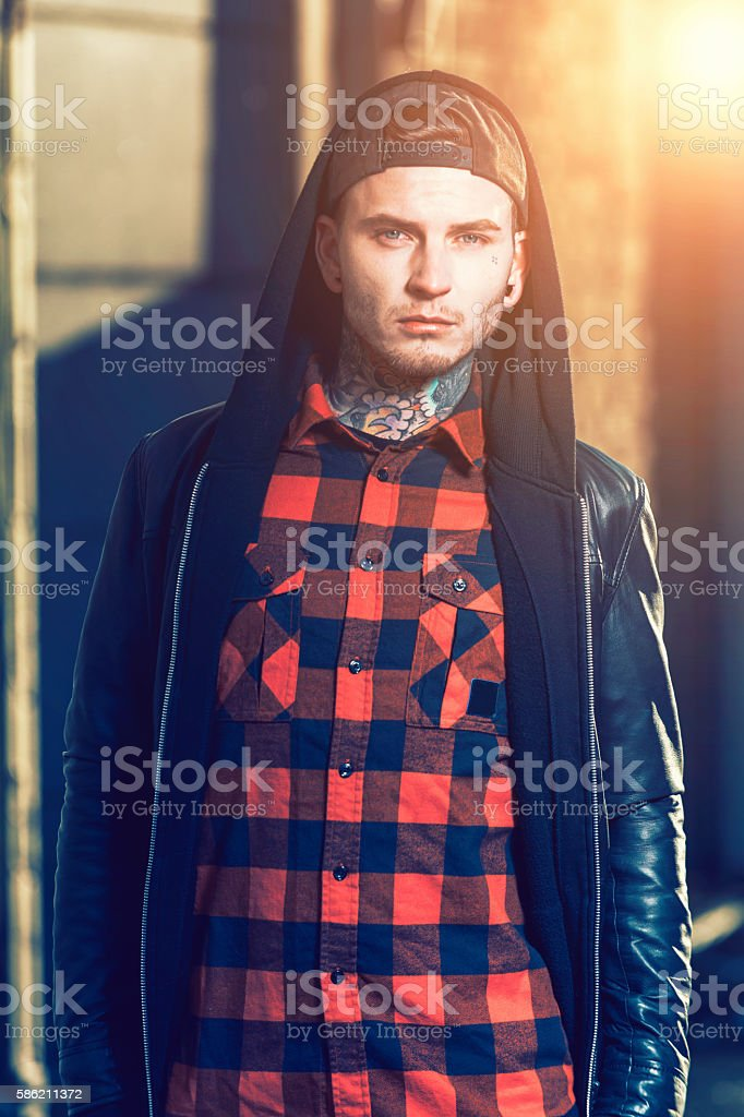 Confident and handsome male fashion model with tattoos on neck stock photo
