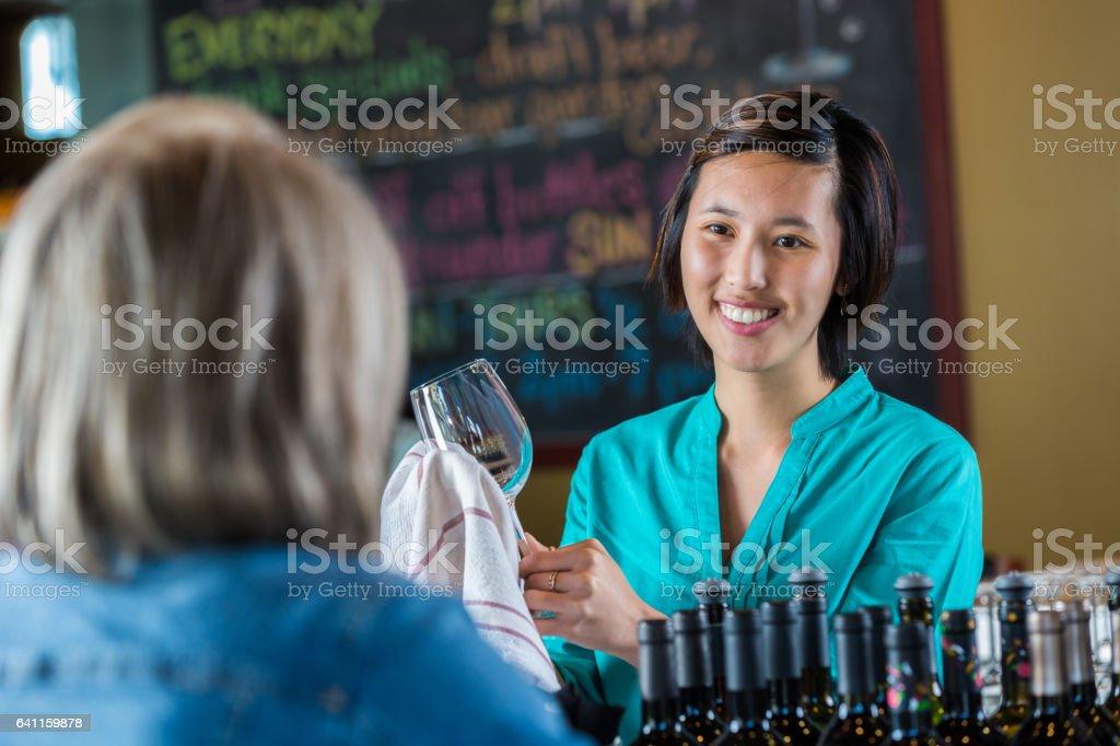 Confident Asian female bartender talks with customer stock photo
