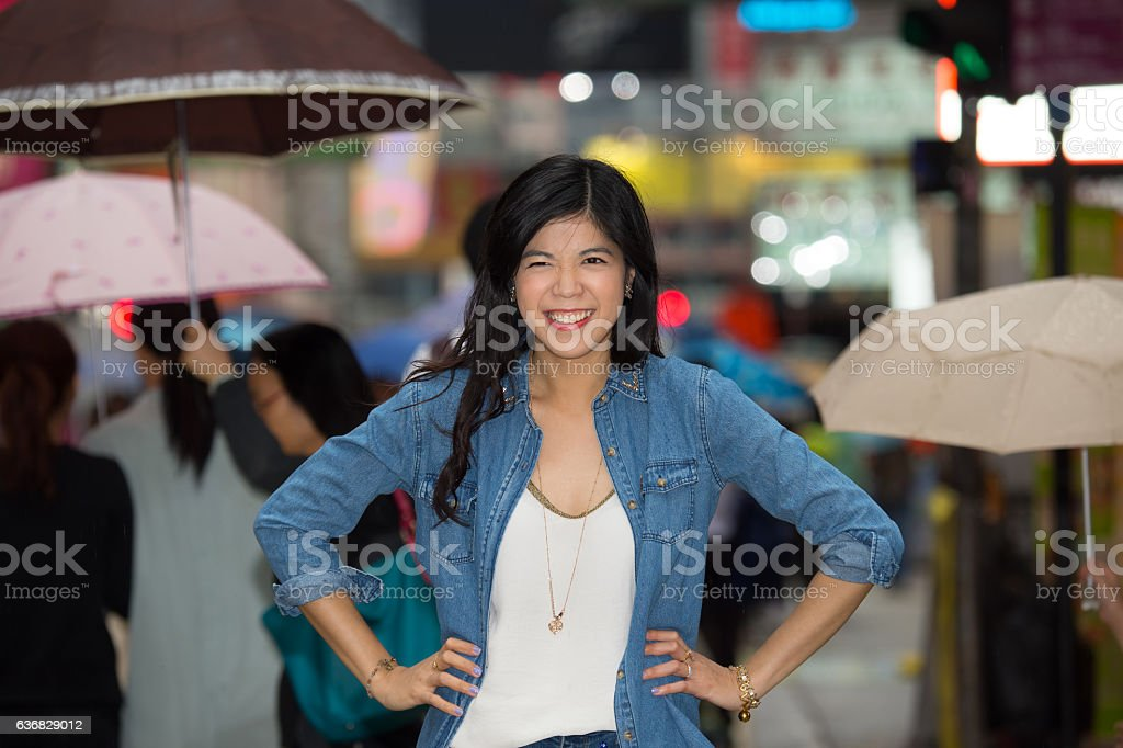 Confident asian woman, in the street, night, making face stock photo