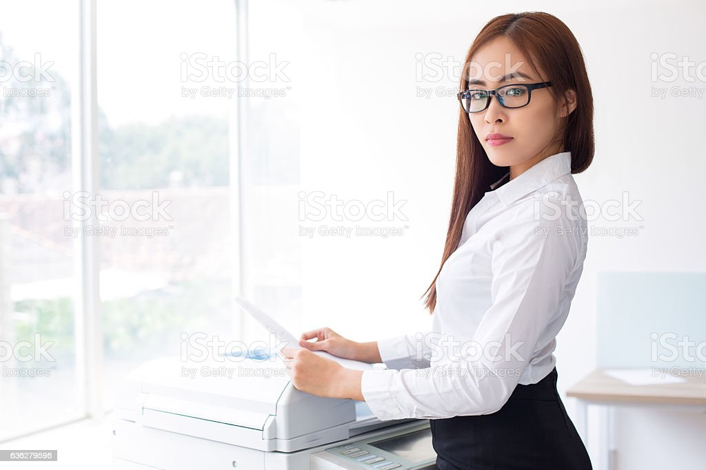 Confident Asian Woman Using Photocopier in Office stock photo