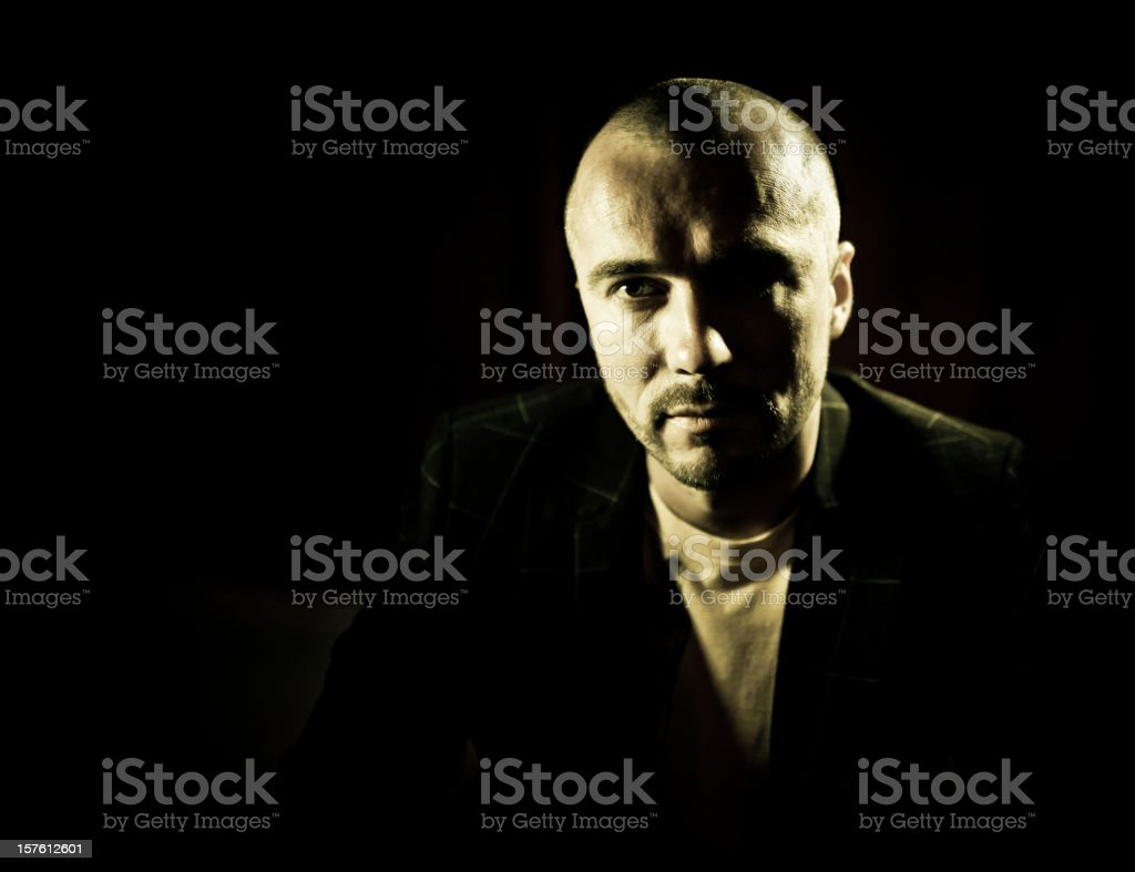 confident bald guy portrait in the dark stock photo