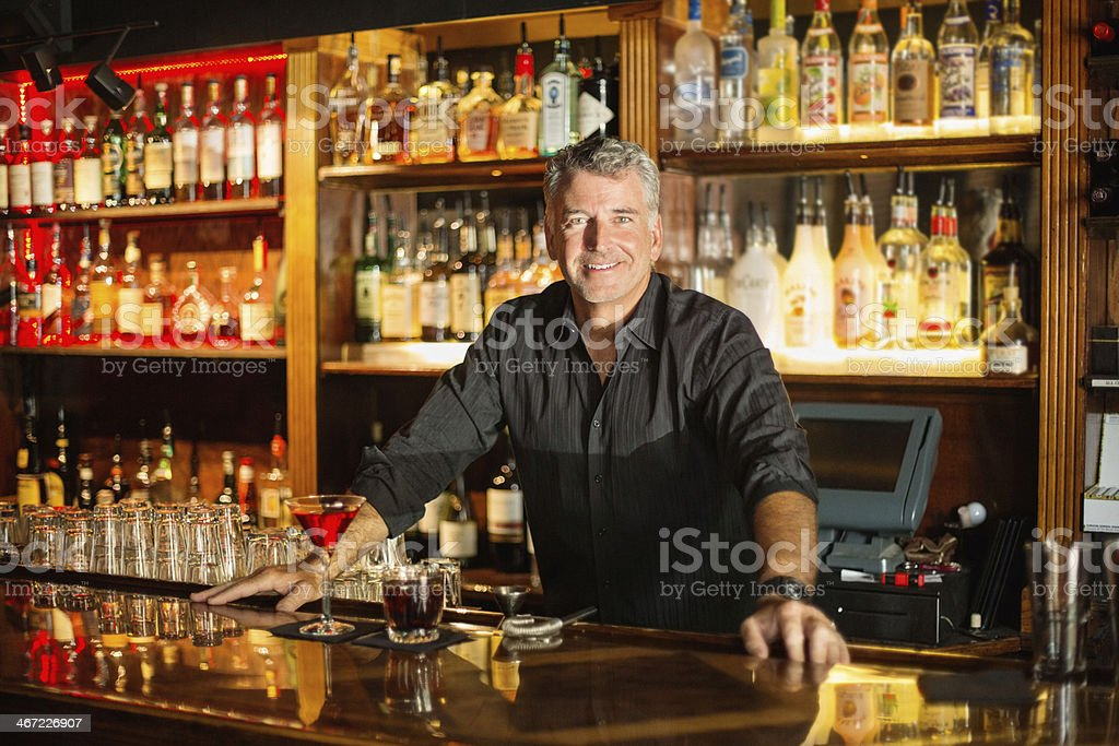 Confident Bartender Leaning At Counter stock photo