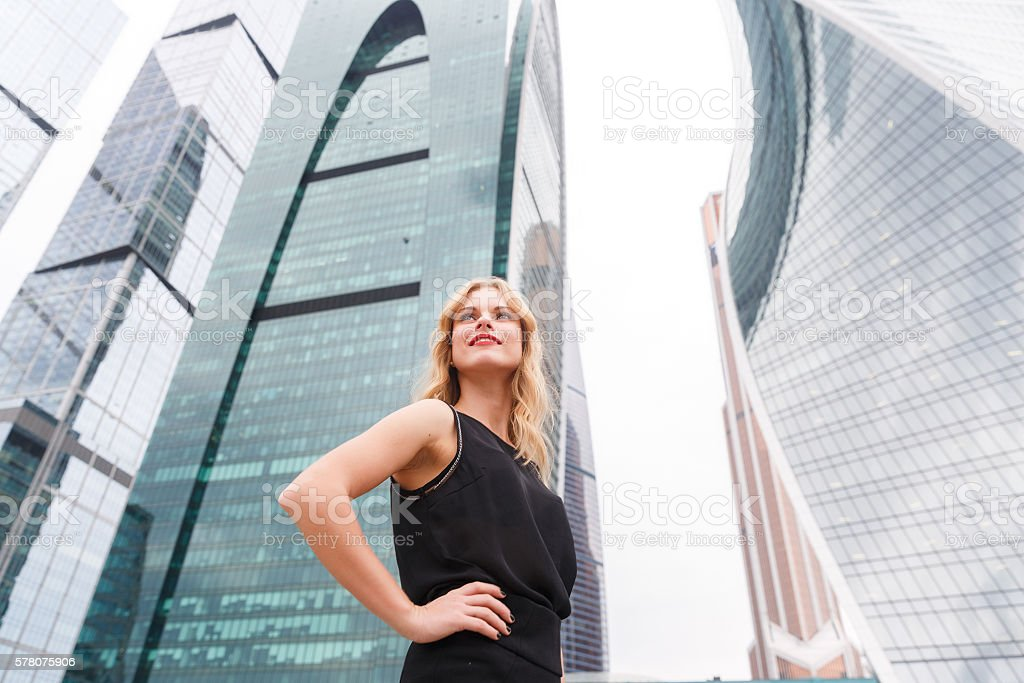 Confident blonde woman with arms akimbo on skyscraper background stock photo