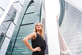 Confident blonde woman with arms akimbo on skyscraper background
