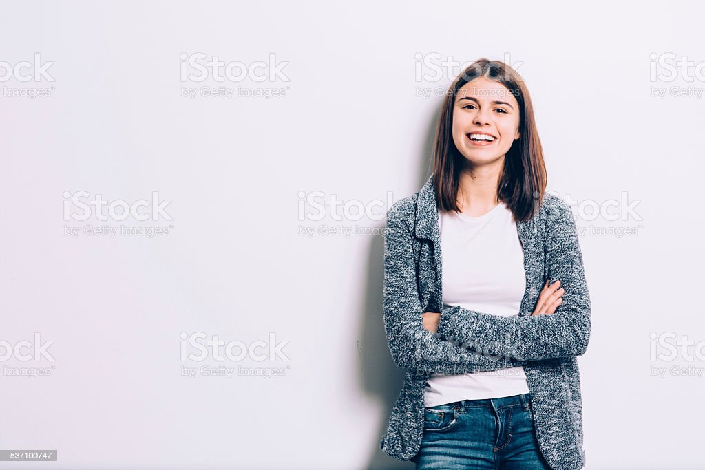 Confident brunette leaning against the wall stock photo