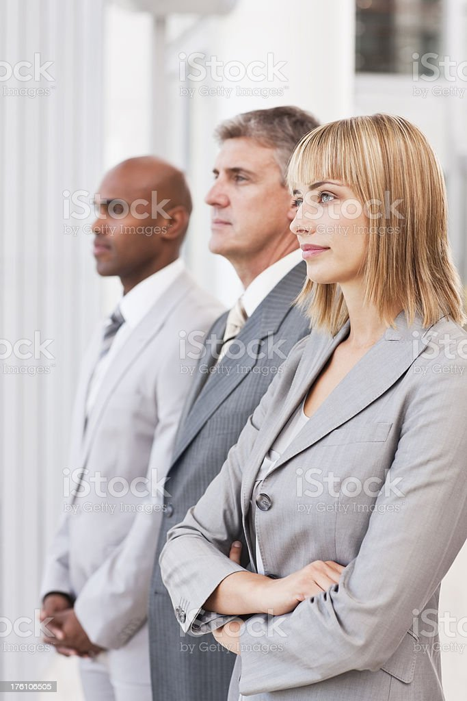 Confident business colleagues standing in a row royalty-free stock photo