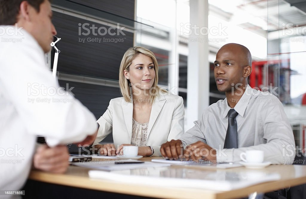 Confident business man discussing plans with colleagues royalty-free stock photo