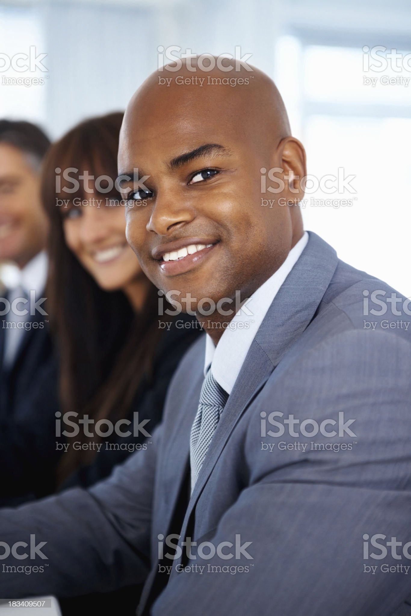 Confident business man with team in background royalty-free stock photo