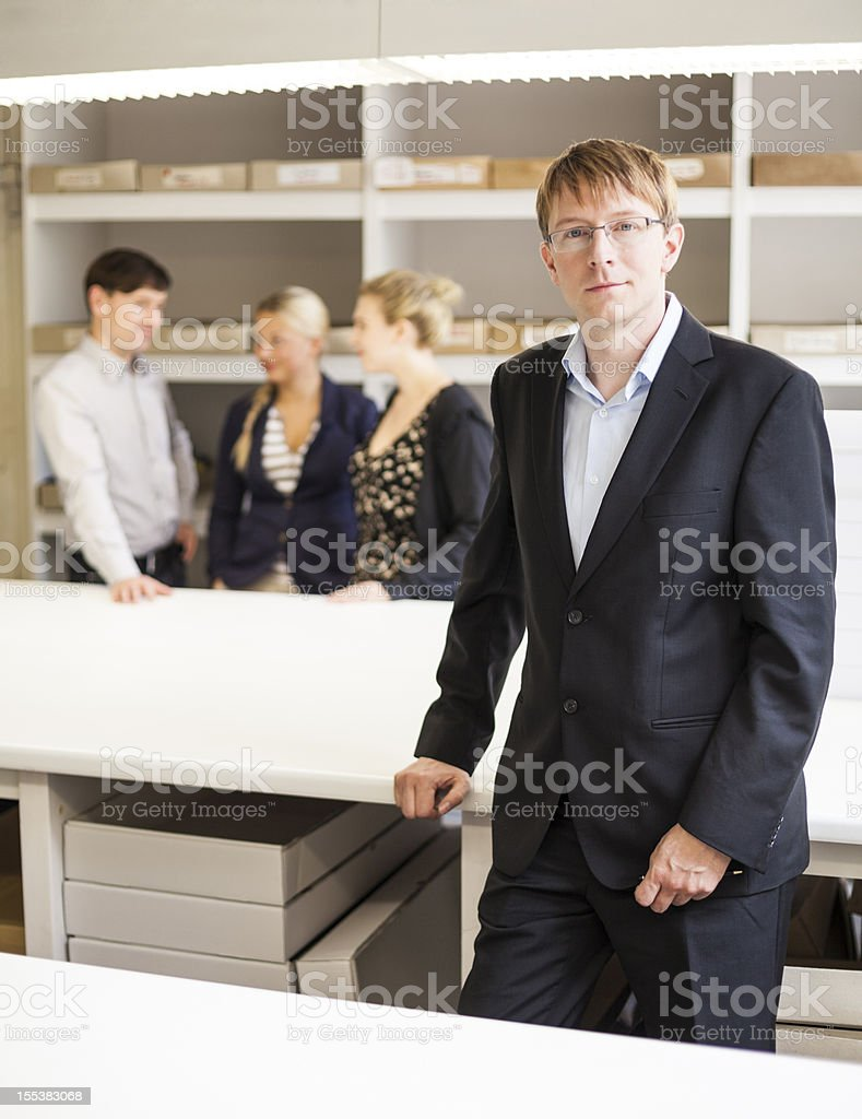 confident business owner with team in background royalty-free stock photo