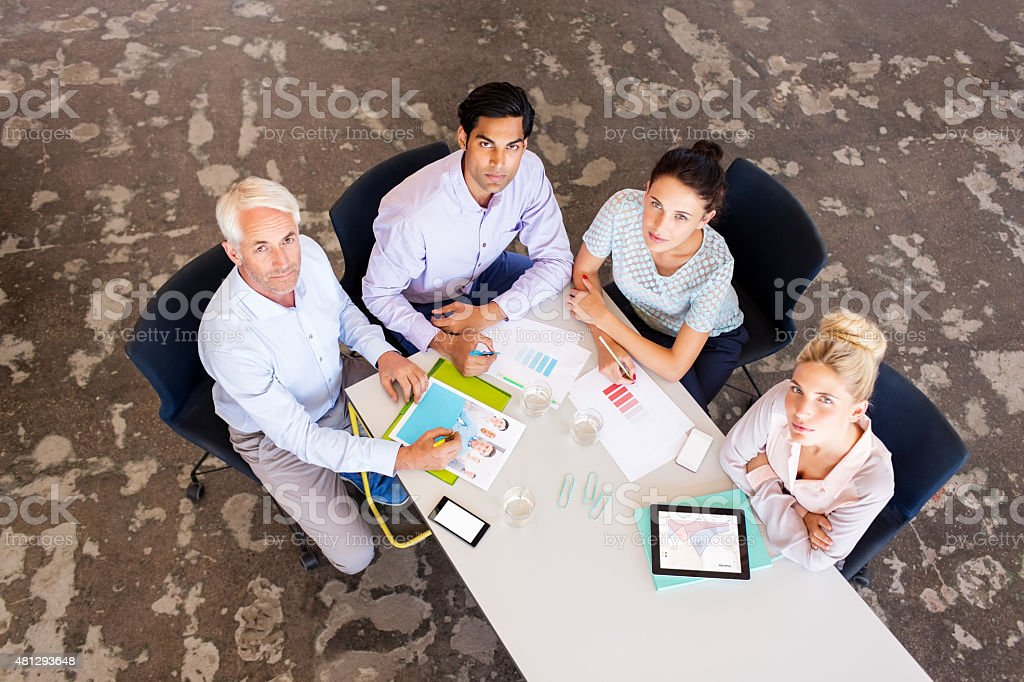 Confident Business Partners At Conference Table stock photo