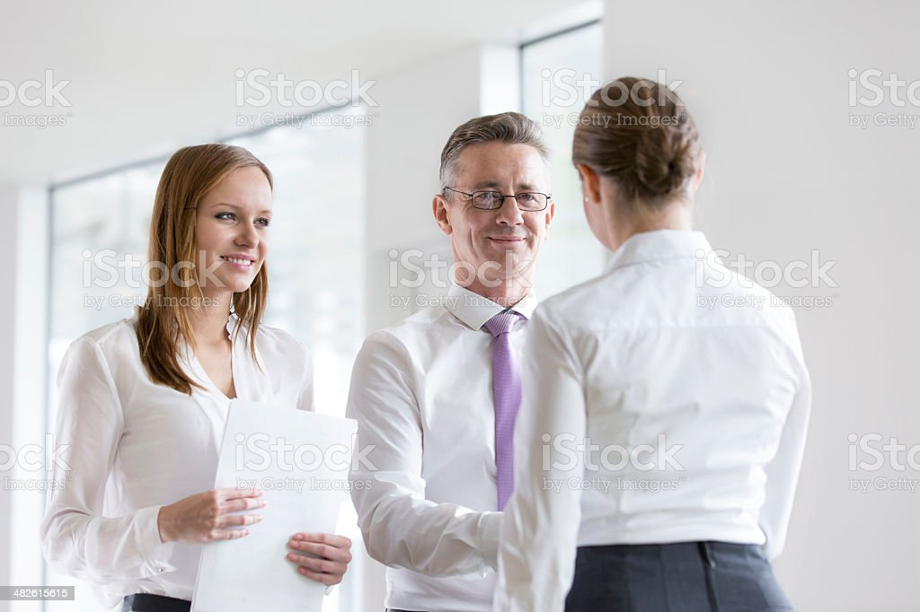 Confident business people shaking hands in office stock photo