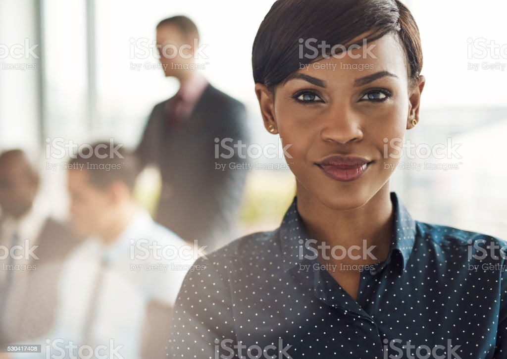 Confident business woman in office with group stock photo