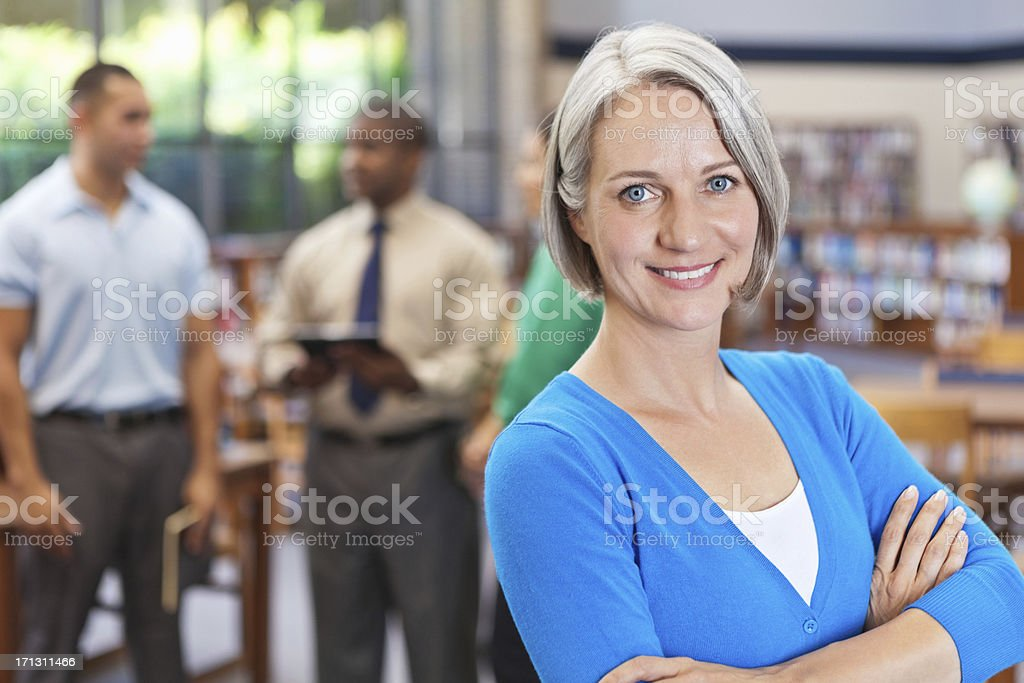 Confident business woman smiling in front of professional team royalty-free stock photo