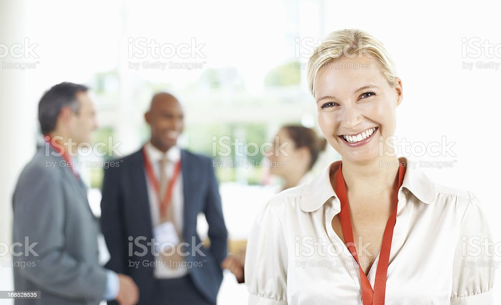 Confident business woman with colleagues in background stock photo