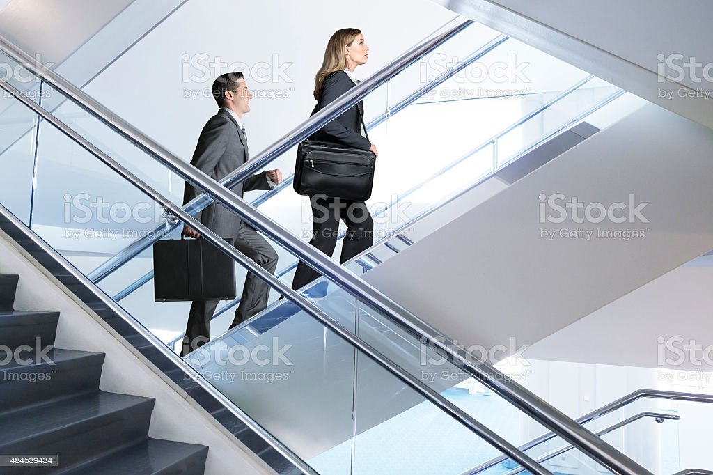 Confident Businessman And Businesswoman walking up flight of stairs stock photo