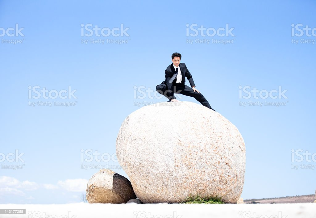 Confident businessman balancing on a boulder royalty-free stock photo