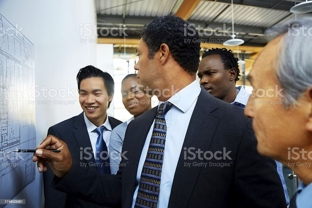 Confident businessman discussing a building project with colleagues royalty-free stock photo