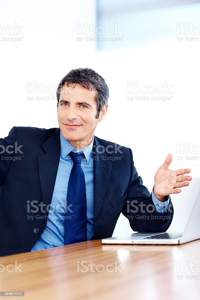 Confident businessman gesturing at his laptop royalty-free stock photo
