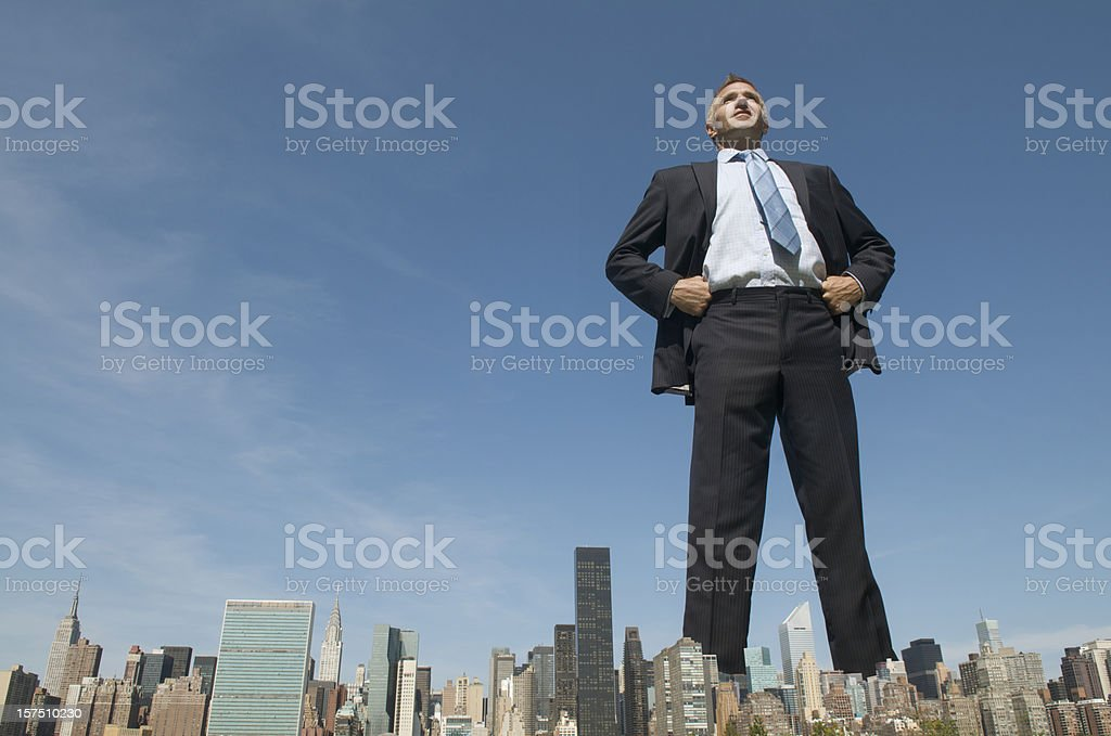 Confident Businessman Giant Towering Over City Skyline stock photo