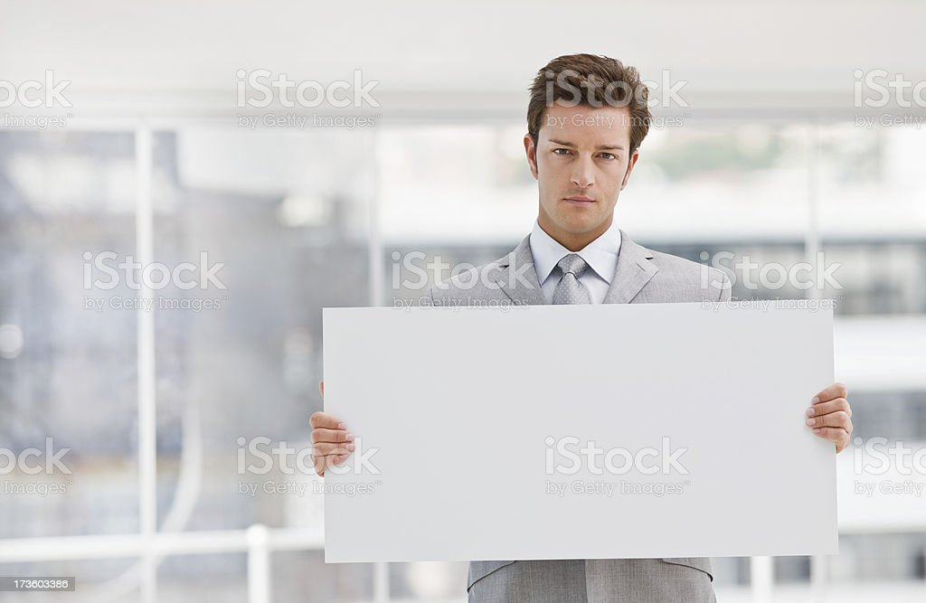 Confident businessman holding white blank card royalty-free stock photo