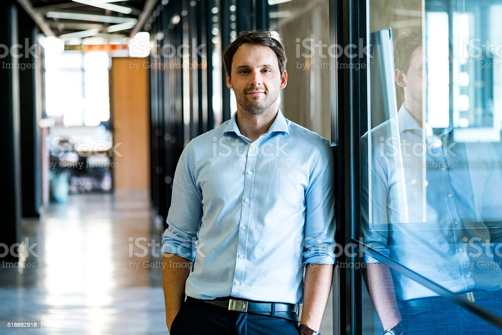 Confident businessman leaning on glass wall in office stock photo