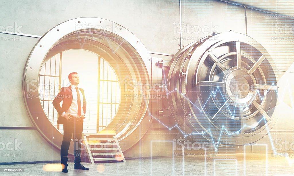 Confident businessman near open vault door with graphs stock photo